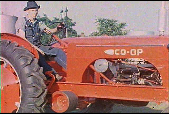 farmer riding co-op tractor, 1950's